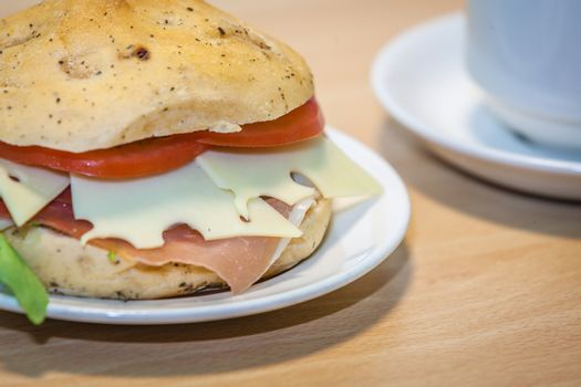 Breakfast ham, cheese and tomato bun on a plate