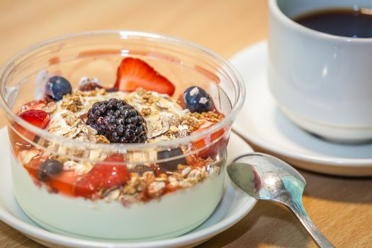Cup of coffee and bowls of freshly prepared natural yoghurt with granola and berries