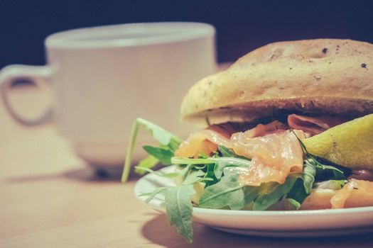 Breakfast bun on a plate, filled with smoked salmon and rocket salad