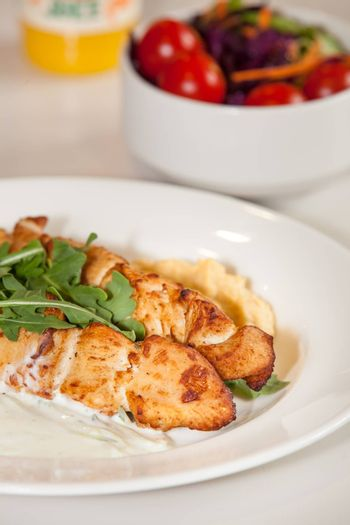 Grilled chicken meat skewers meal with rocket salad leaves, youghurt and peanut sauce
