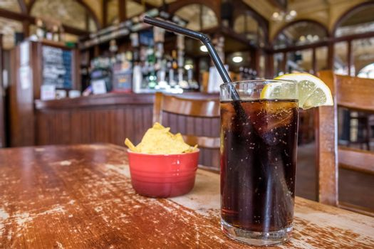 Glass containing cola with lemon and small bowl of nachos in the background