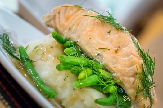 Roast salmon main course served with mashed potatoes and green beans