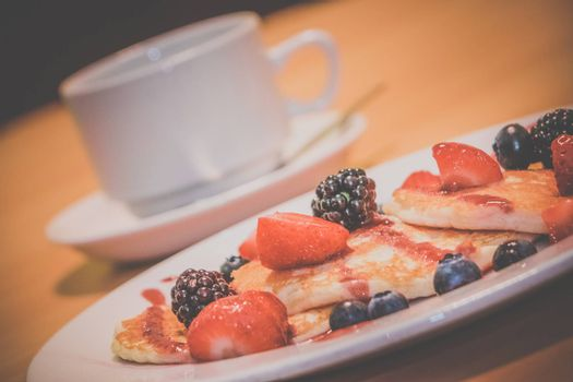 Breakfast meal consisting of pancakes with maple syrup, jam and berries