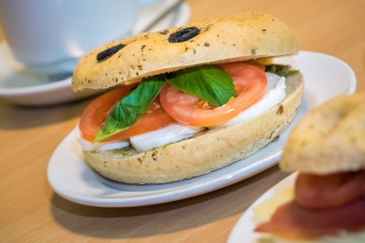 Breakfast bun on a plate, filled with mozzarella, tomato and basil