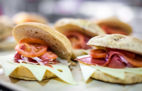 Breakfast buns on a plate, filled with cheddar cheese, prosciutto ham and tomatoes