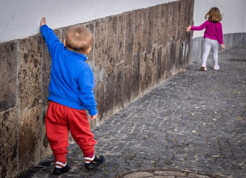 Little kids - brother and sister walking along the home wall in Spain