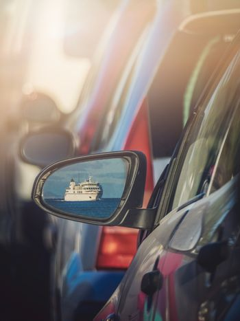 Car mirror reflection of a large passenger ferry carrying cars and passengers arriving sailing between the port of Playa Blanca in Lanzarote and Corralejo in Fuerteventura, Canary Islands, Spain