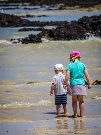 Little boy and girl standing in water waiting for wave to come on the beach in summer