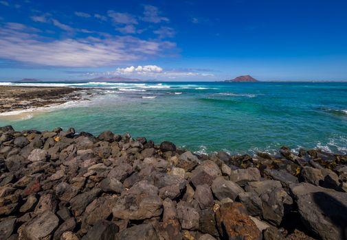 Rocky coast in Corralejo, Fuerteventura, Canary Island, Spain with Los Lobos Island in the background