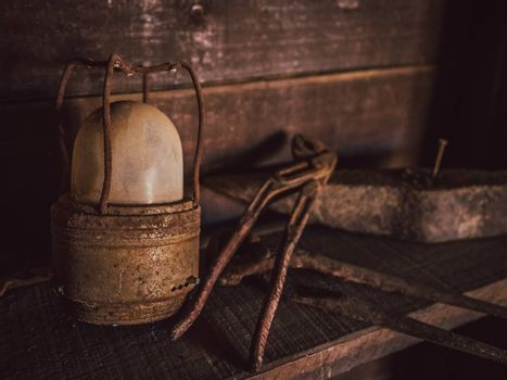 Old rusted lamp and tools in a shed in a village