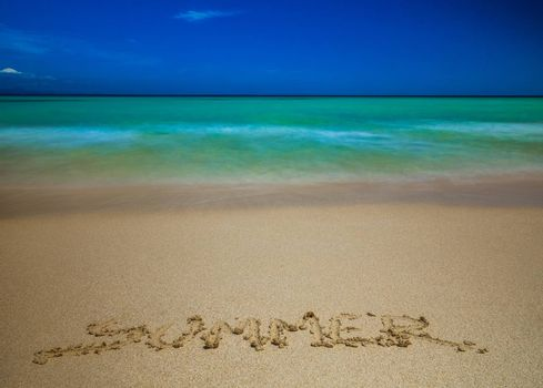 Word summer written on sand on a beach in front of beautiful turquoise blue sea in Corralejo Dunes National Park in Fuerteventura, Canary Island, Spain