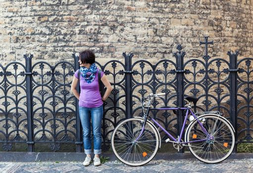 Young woman in purple shirt and purple vintage bicycle on the street in Prague, Czech Republic