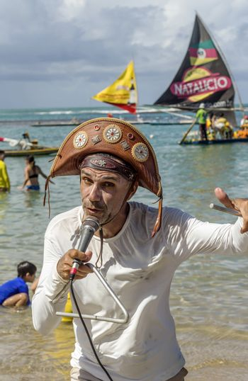Pernambuco, Brazil July 6, 2016: An unidentified singer in Chicken Beach with typical sail boats behind in Ipojuca City near barrier reef, northeast Brazil