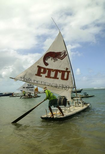Pernambuco, Brazil July 6, 2016: An unidentified fisherman in Chicken Beach with typical sail boats in Ipojuca City near barrier reef, northeast Brazil