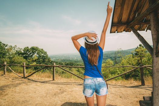 Cheerful woman on summer travel vacation standing by viewpoint with outstretched arm. Rear view.