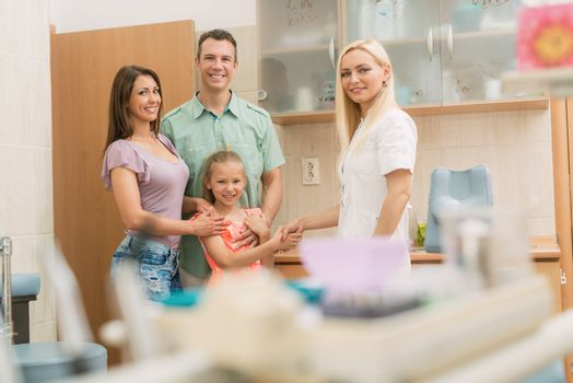 Little girl and her parents visiting dentist. The little girl is shaking hand with female dentist and smiling. Looking at camera.