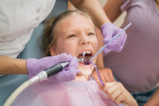 Beautiful little girl at visit in the dentist office. She is sitting on a chair and dentist polished teeth on her.