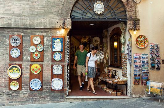 SIENA, ITALY - JUNE 29, 2016: Tourists visiting traditional art and souvenir shop in old town of Siena, Italy
