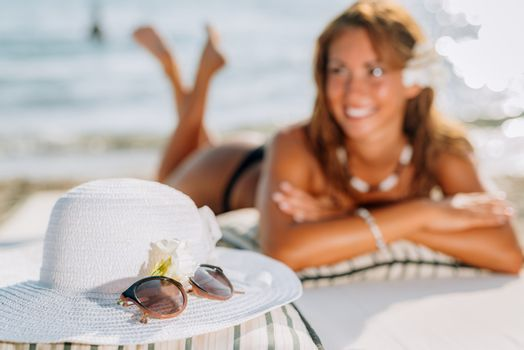 Beautiful young woman enjoying on the beach. She is smiling and looking away. In foreground is white summer hat and sunglasses. Selective focus. Focus on foreground.