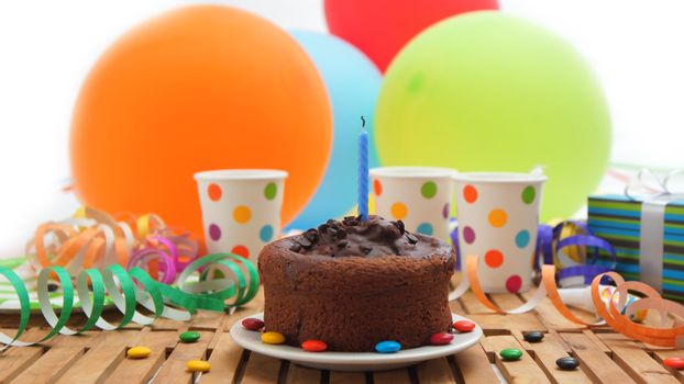 Chocolate birthday cake with a blue candle extinguished on rustic wooden table with background of colorful balloons, gifts, plastic cups with candies and white wall in the background