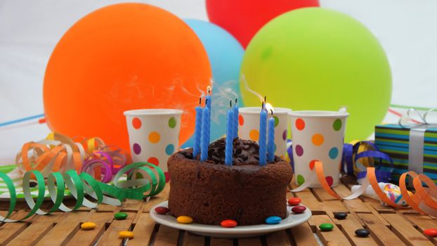 Chocolate birthday cake with a blue candles extinguished on rustic wooden table with background of colorful balloons, gifts, plastic cups with candies and white wall in the background