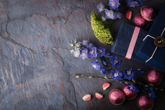 Spring gift with candy and flowers on a blue stone background