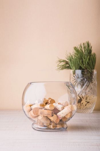 Vase with corks and coniferous branch on the table