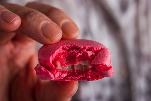 Woman holds bitten off macaroon in in her hand