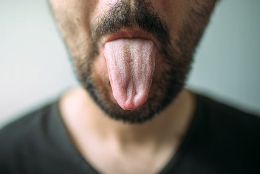 Adult unshaven man sticking tongue out