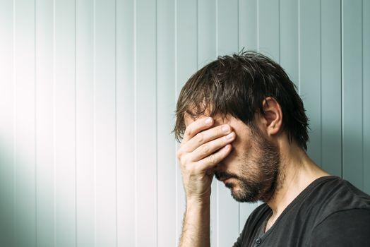 Profile portrait od miserable troubled man
