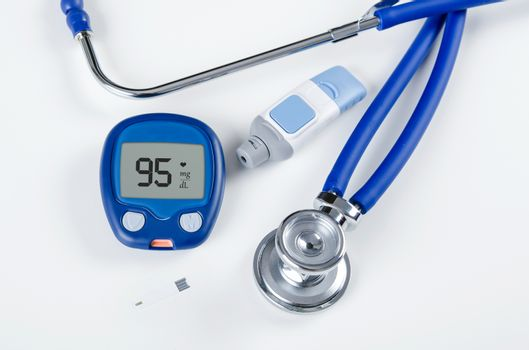 Diabetic test kit and stethoscope on white background
