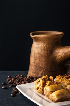 Wooden cezve with baklava on the dark table