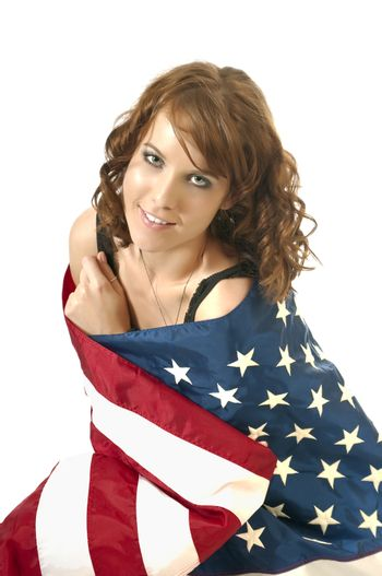 Pretty young woman wrapped in an American flag showing her 4th of July spirit and patriatisim.