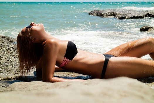 Beautiful young woman relaxing on the beach. She is lounging and sunbathing on the rocks.