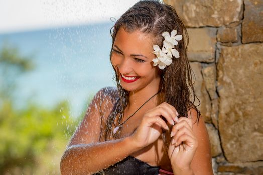 Beautiful young woman enjoying under a shower on the beach.