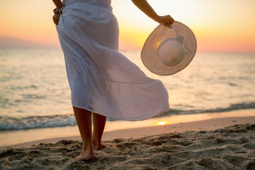 Woman in white dress enjoying sunset on the beach and holding white hat. Rear view.