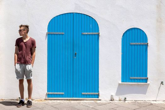 Teenage boy with sunglasses standing relaxed and looking. Mediterranean style white building with closed blue colored doors and window in background
