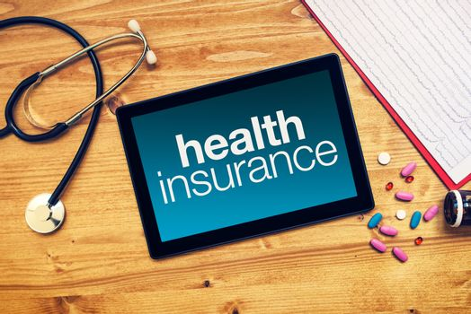 Health insurance title on tablet computer placed on doctors desk
