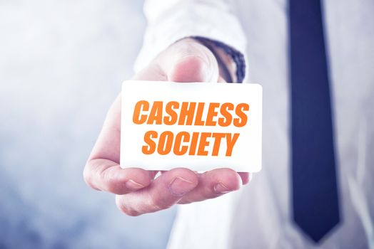 Businessman holding card with Cashless society title