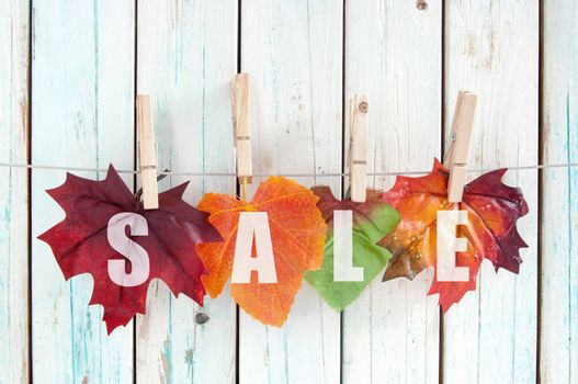 Sales autumn leaves hanging on a line with pegs