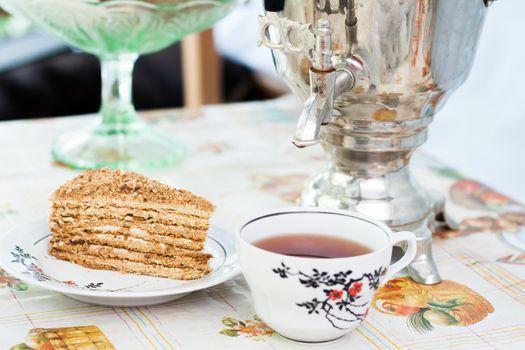 piece of cake honey cake on a plate, a cup of tea and a samovar
