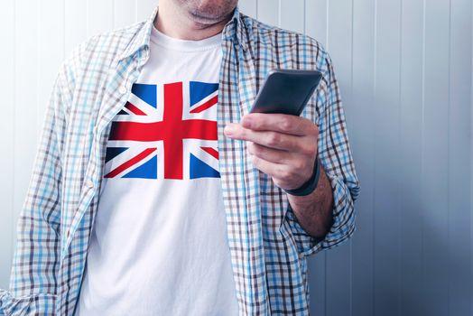 Man with United Kingdom flag on shirt using mobile phone