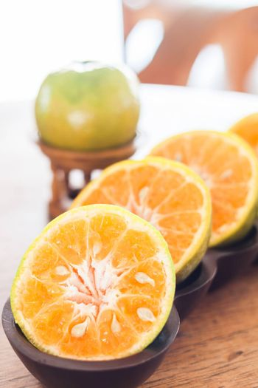 Slice of fresh orange in wooden tray, stock photo