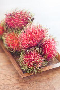 Fresh rambutans on wodden tray, stock photo