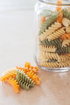 Raw fusilli pasta with glass bottle, stock photo