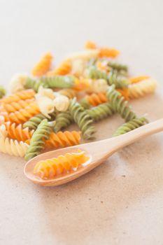 Raw fusilli pasta with wooden spoon, stock photo