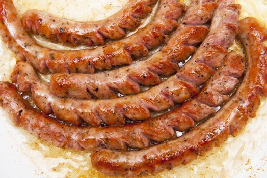 Sausages friyng in the frying pan