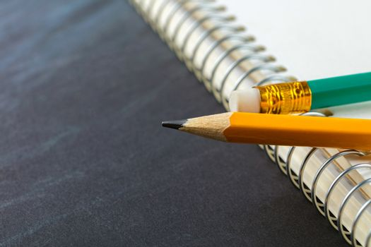 sharpened pencil and a notebook