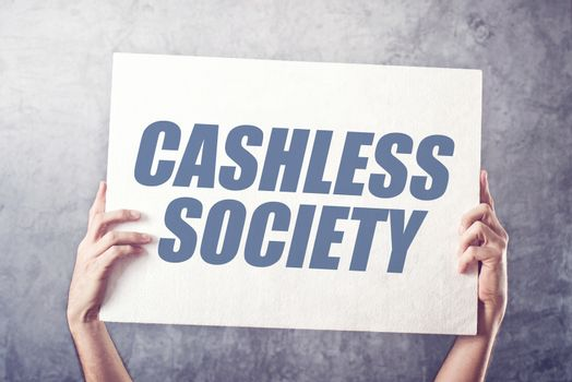 Hands holding banner with Cashless society title