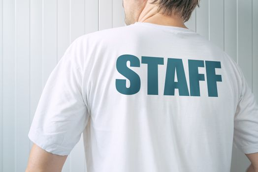 Man wearing white t-shirt with title Staff on back